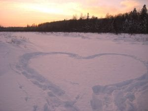 footprints in snow making the shape of a heart